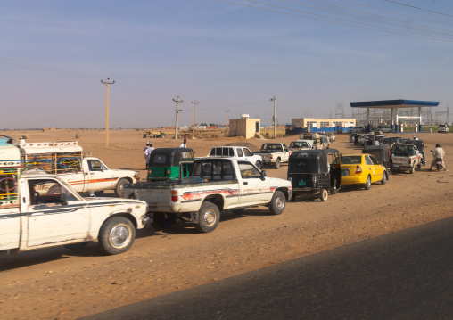 Sudanese people in their cars queue on line at a gas station during the fuel shortages, Northern State, Meroe, Sudan