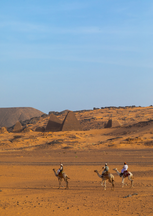 Sudanese men and their camels in front of the pyramids of the kushite rulers at Meroe, Northern State, Meroe, Sudan