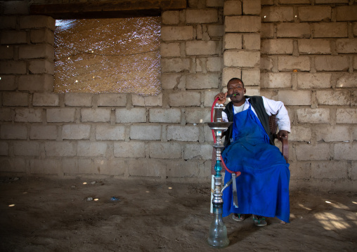 Beja man smoking water pipe, Red Sea State, Suakin, Sudan