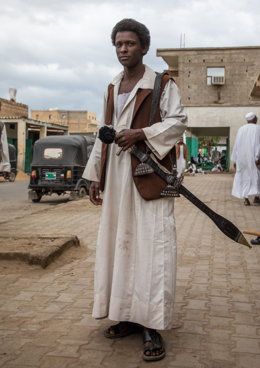 Beja tribe warrior with his sword in the street, Red Sea State, Port Sudan, Sudan