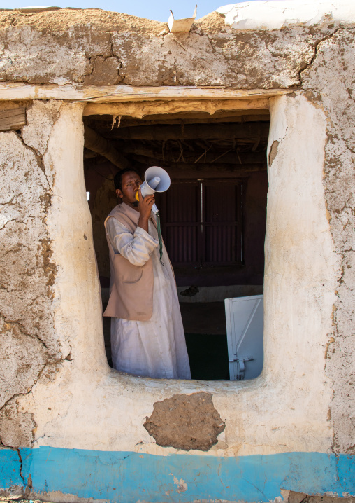 Muezzin making the call to prayers in a small mosque with a megaphone