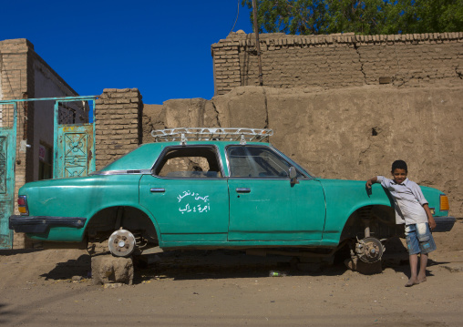 Sudan, Northern Province, Dongola, boy in front of an old green car