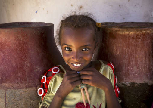 Sudan, Northern Province, Gunfal, smiling sudanese girl in front of water jars