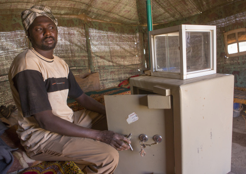 Sudan, Khartoum State, Alkhanag, man buying gold in front of his safety box