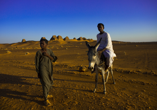 Sudan, Kush, Meroe, kids in front of the pyramids and tombs in royal cemetery
