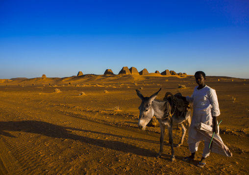 Sudan, Kush, Meroe, kid with his donkey in front of the pyramids and tombs in royal cemetery, meroe
