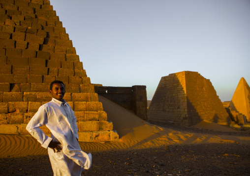 Sudan, Kush, Meroe, young sudanese man in front of the pyramids and tombs in royal cemetery