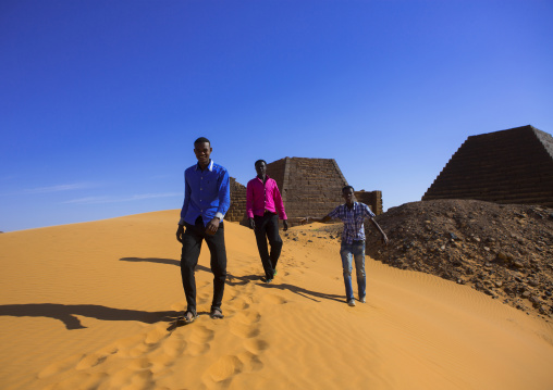 Sudan, Kush, Meroe, young men in front of pyramids and tombs in royal cemetery