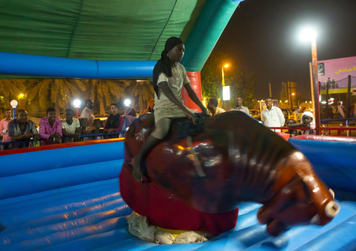 Sudan, Red Sea State, Port Sudan, girl riding a bull in a fun fair
