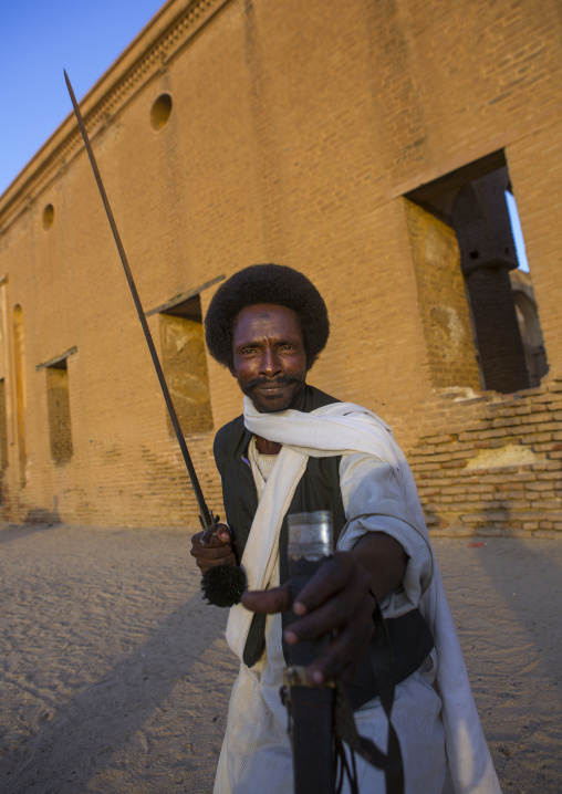 Sudan, Kassala State, Kassala, beja tribe man dancing in front of the khatmiyah mosque at the base of the taka mountains