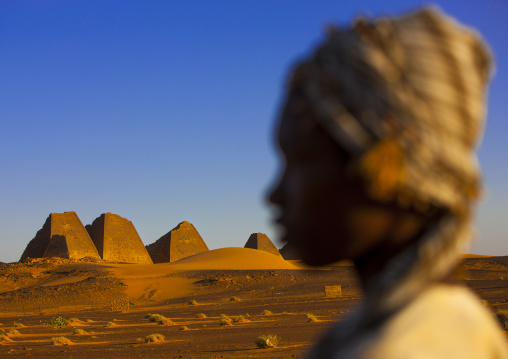 Sudan, Kush, Meroe, kid in front of the pyramids and tombs in royal cemetery