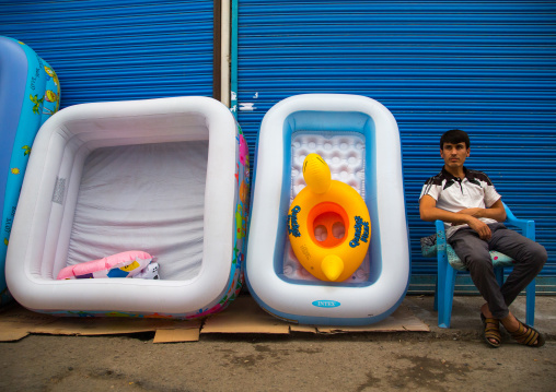 Tajik man selling plastic pools for children in the street, Gorno-Badakhshan autonomous region, Khorog, Tajikistan
