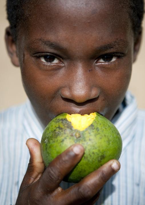Kid eating mango, Pemba, Tanzania