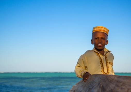 Tanzania, Zanzibar, Kizimkazi, young muslim boy in school uniform on beach