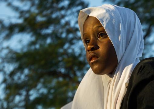 Tanzania, Zanzibar, Kizimkazi, young muslim girl in school uniform running on beach