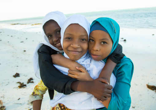 Tanzania, Zanzibar, Kizimkazi, young muslim girls in school uniform running on beach