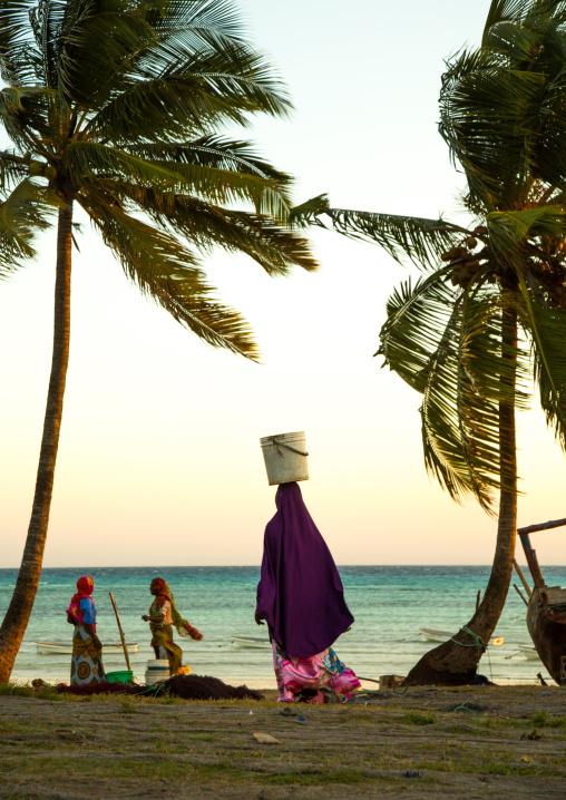 Tanzania, Zanzibar, Kizimkazi, women carrying fishes in a bucket on their heads