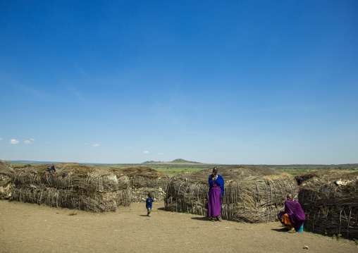 Tanzania, Ashura region, Ngorongoro Conservation Area, maasai women with child outside their home