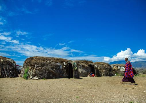 Tanzania, Ashura region, Ngorongoro Conservation Area, maasai cwoman passing in front oh her home