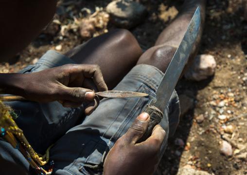 Tanzania, Serengeti Plateau, Lake Eyasi, hadzabe bushman making the arrow for a hunting bow