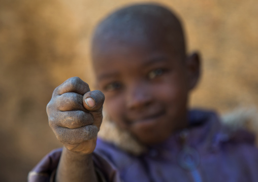 Tanzania, Serengeti Plateau, Lake Eyasi, hadzabe tribe boy showing how to say the number five with the fist