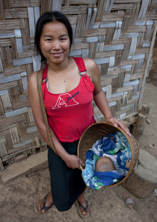 Karen woman carrying her baby in a basket, North thailand