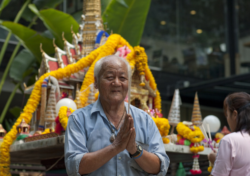 Man in a temple in the street, Bangkok, Thailand