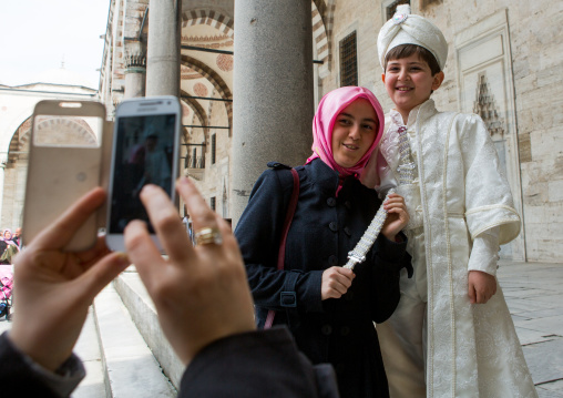 Young turkish boy in the ceremonial circumcision outfit posing with his mother outside the the Blue mosque, Sultanahmet, istanbul, Turkey