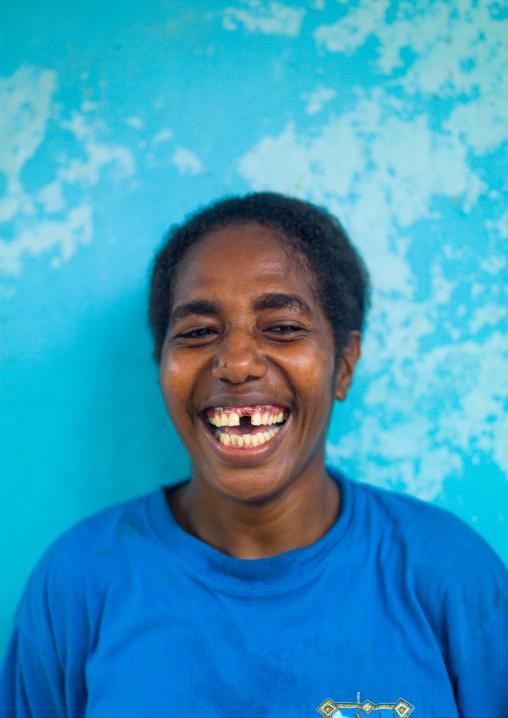 Ni-Vanuatu woman laughing in front of a blue wall, Malampa Province, Malekula Island, Vanuatu