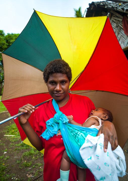Woman with an umbrella carrying her sleeping baby, Malampa Province, Malekula Island, Vanuatu