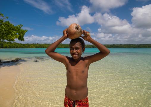 Young boy of the Ni-Vanuatu people with a coconut on his head, Sanma Province, Espiritu Santo, Vanuatu
