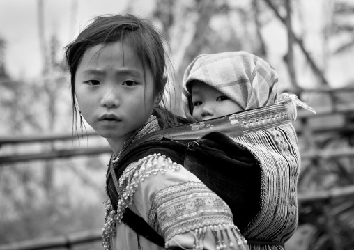Flower hmong girl carrying her baby sister on her back, Sapa, Vietnam