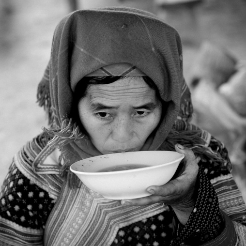 Flower hmong woman drinking a bowl of soup, Sapa market, Vietnam