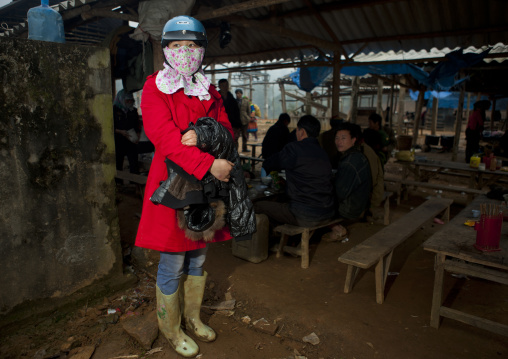 Elegant woman with a crash helmet and a scarf on the face, Sapa market, Vietnam