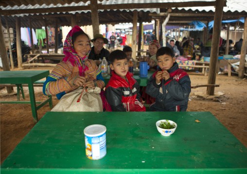 Flower hmong woman and her sons sitting on a table for lunch, Sapa market, Vietnam