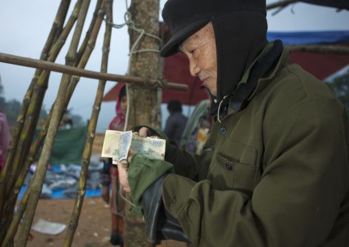 Old man showing the money he earned, Sapa, Vietnam