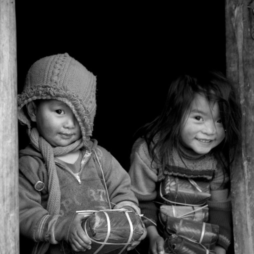 Black hmong kids holding wrapped rice cakes for tet, Sapa, Vietnam