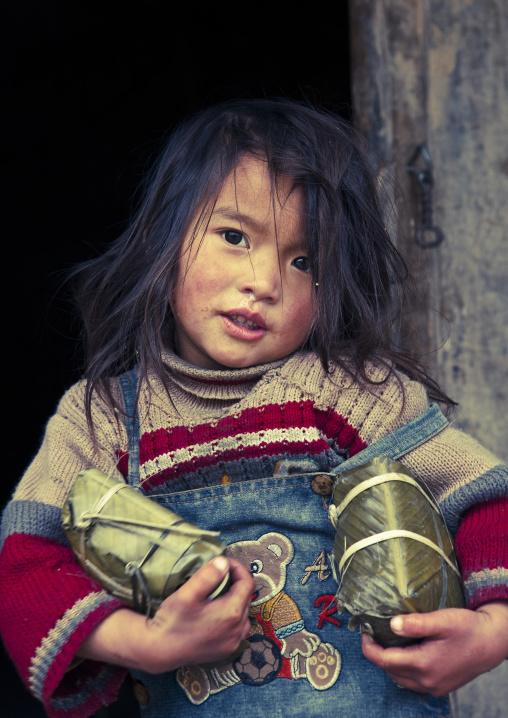 Black hmong girl holding holding wrapped rice cakes for tet, Sapa, Vietnam