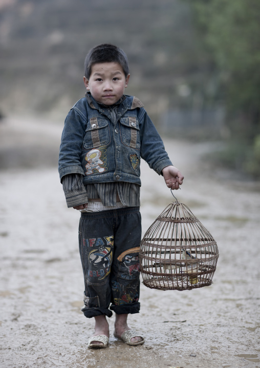 Black hmong boy holding a caged bird, Sapa, Vietnam