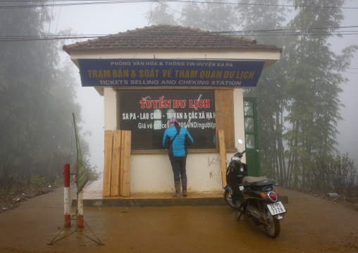Woman paying the entrance fee of the national park at tha ticket office, Sapa, Vietnam