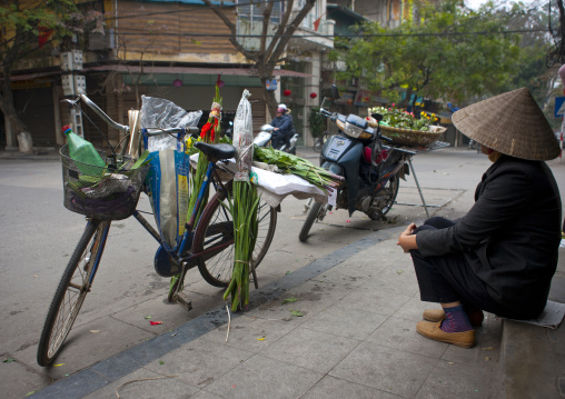 Woman sitting next to his bike in the street, Hanoi, Vietnam