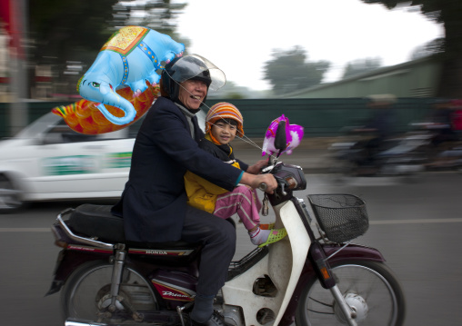 Man and girl on a moped in hanoi, Vietnam
