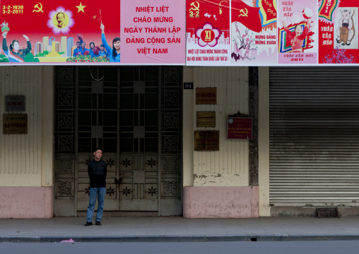 Man under propaganda panels of the communist party, Hanoi, Vietnam
