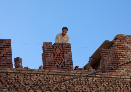 Man Chewing Qat While Adjusting Bricks On A Roof, Sanaa, Yemen