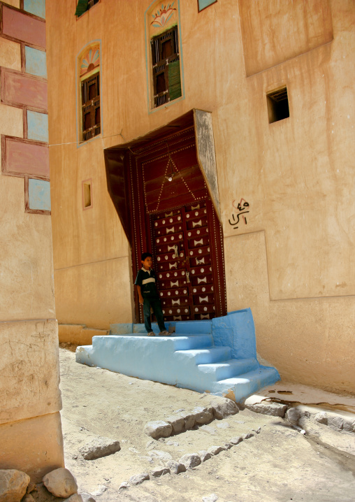 Boy Standing On The Blue Doorstep Of The Wooden Carved Door Of A Typically Painted Building, Wadi Doan, Yemen