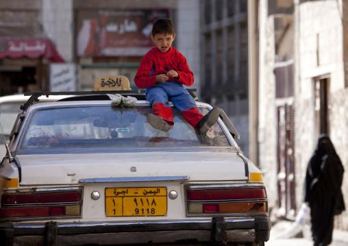 Kid Wearing A Spiderman Suit Sitting On The Top A Car In A Street Of Sanaa, Yemen