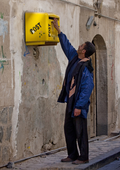 Man Posting Letters In A Strangely Highly Placed Yellow Mailbox, Sanaa, Yemen