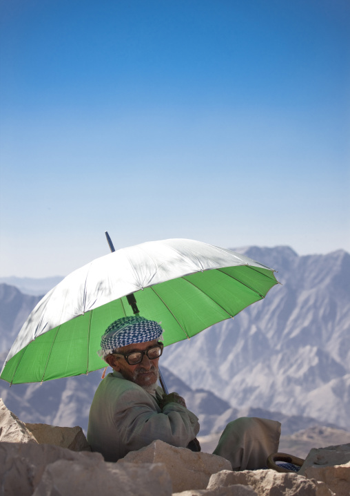 Old Man With Glasses Sitting Under The Shade Of A Green Umbrella In The Mountain, Hababa, Yemen