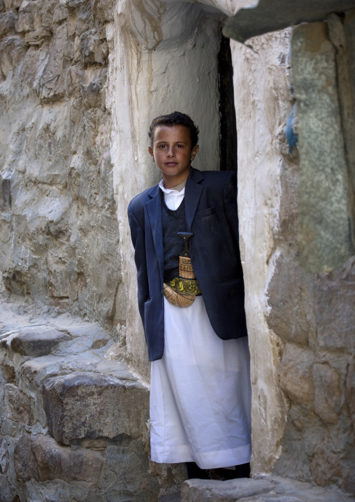 Young Boy In Adult Clothes And Wearing Jambiya In Front Of A Door, Thula, Yemen