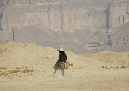 Hadramaut Woman With  A Tall Cone Hat Riding A Donkey In The Dust, Yemen